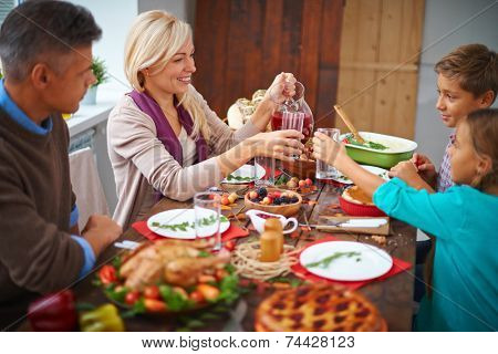 Portrait of modern family of four having festive dinner on Thanksgiving day