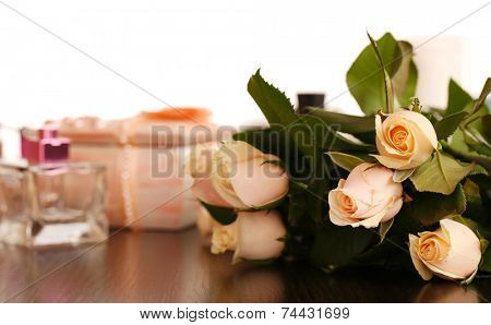Beautiful roses, perfumes on table near mirror