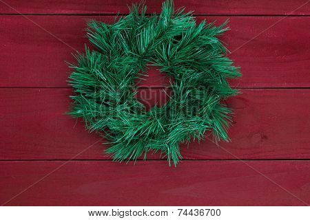 Christmas wreath hanging on dark antique red wood background