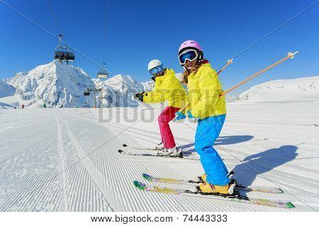 Ski, skier, snow and fun - family enjoying winter vacations