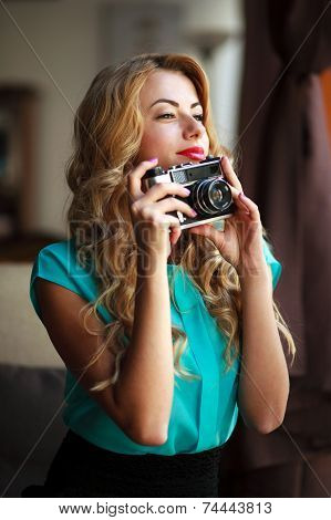 Beautiful Young Woman Photographer Taking Pictures With Retro Film Camera Indoors