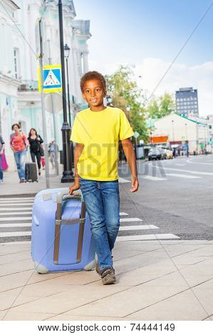 African boy holding pink luggage and walking