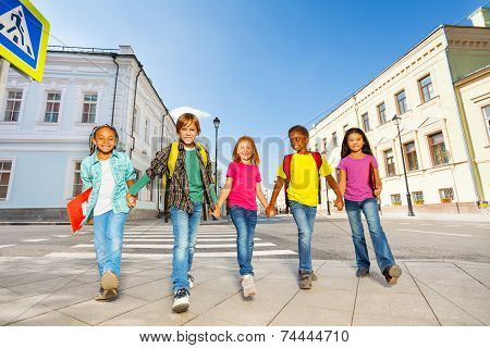 International schoolchildren walk and hold hands