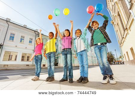 Below view of multinational kids with balloons