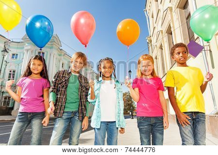 Multinational children with balloons standing