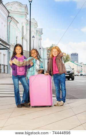 Three smiling girls stand with map and luggage