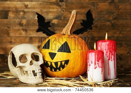 Halloween pumpkin, skull and bloody candles on wooden background