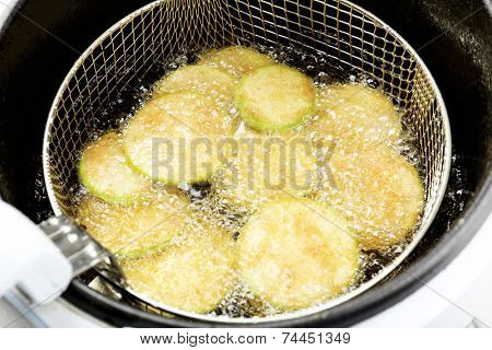 Zucchini in deep fryer, closeup