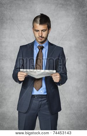 Surprised Businessman Reading A Newspaper Article