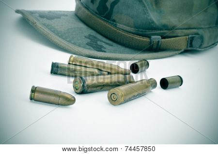 a camouflage cap and some bullets and bullet shells