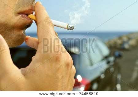 closeup of a man with a burning cigarette in his mouth while is waiting besides a car parked next to a no traffic road