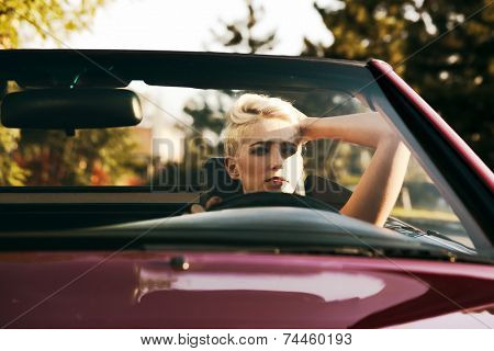 blond young woman in cabriolet
