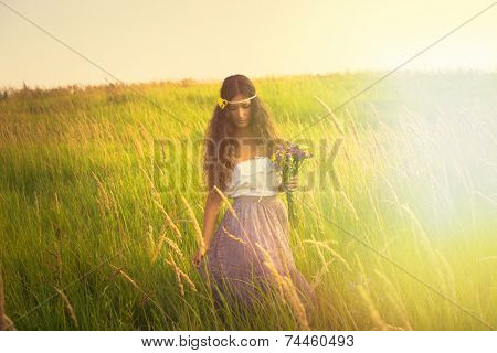 young beautiful woman with long curly hair hold in hand a bouquet of wild flowers in romantic clothes  walk in light at grass field