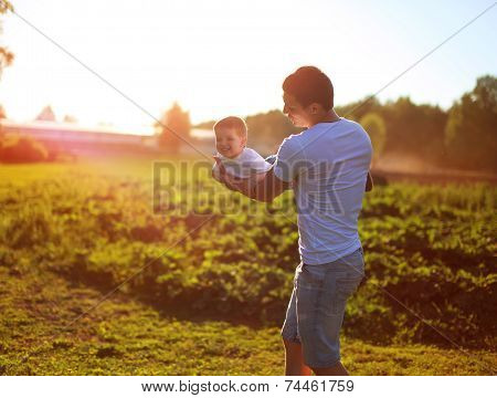 Happy Child, Dad And Son Having Fun, Holding On Hands On A Sunset Background