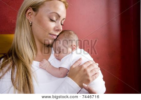 Mother holding newborn baby in rocking chair