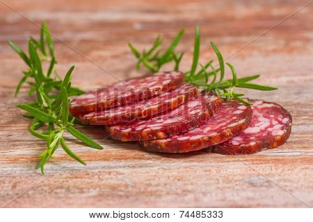 salami slices with pepper and rosemary