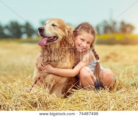 happy little girl with her dog golden retriever in rural areas in summer