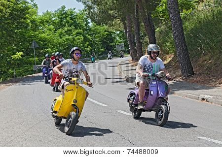 Group Of Bikers Riding A Vintage Italian Scooters
