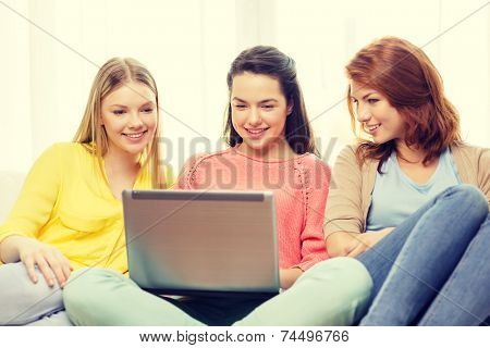 friendship, technology and internet concept - three smiling teenage girls with laptop computer at home