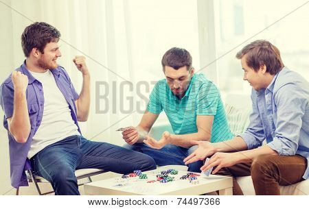 leisure, games and lifestyle concept - happy three male friends playing poker at home