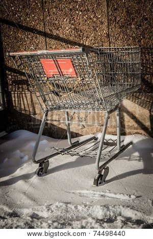 An unused shopping cart sitting in the snow at the side of the mall.