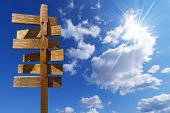 foto of crossroads  - Wooden old brown crossroad sign on a blue sky with clouds - JPG