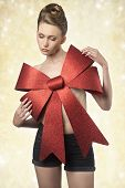 image of adornment  - creative christmas portrait of sexy woman adorned like a gift with big red bow on the breast and elegant hair - JPG