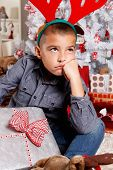 stock photo of sad christmas  - Portrait Of A Sad Little Boy With a Christmas Present - JPG