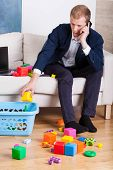 foto of toy phone  - Elegant man cleaning up toys while talking on the phone - JPG