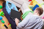 foto of babysitting  - Man using laptop sitting on the floor in a messy living room of laundry baskets and children