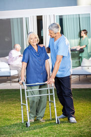 picture of zimmer frame  - Portrait of senior woman being assisted by male caretaker in using Zimmer frame at nursing home lawn - JPG
