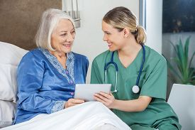 picture of nursing  - Happy female nurse and senior woman discussing while using tablet PC in bedroom at nursing home - JPG