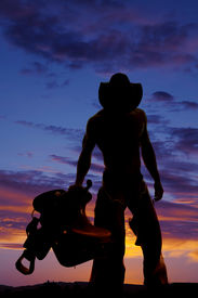 picture of western saddle  - a silhouette of a cowboy holding on to his saddle looking down - JPG