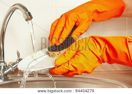 Hands in gloves wash the plate under running water in kitchen