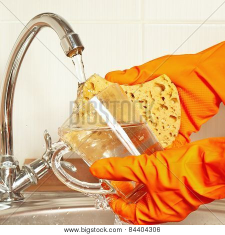 Hands in gloves with sponge wash dirty glass under running water