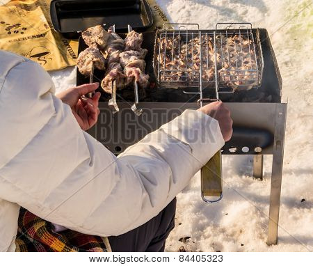 Woman Tending A Barbecue In Winter