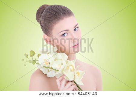 Portrait Of Young Beautiful Woman With Orchid Flower Over Green