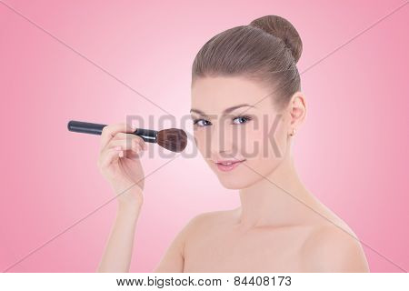 Portrait Of Young Beautiful Woman Applying Rouge Or Powder With Make Up Brush Over Pink