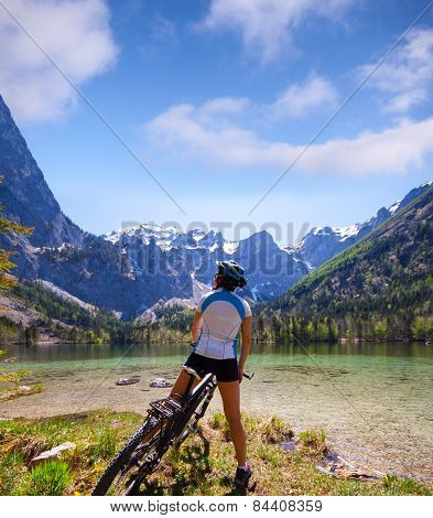 Young woman riding a bike beside Alpine lake
