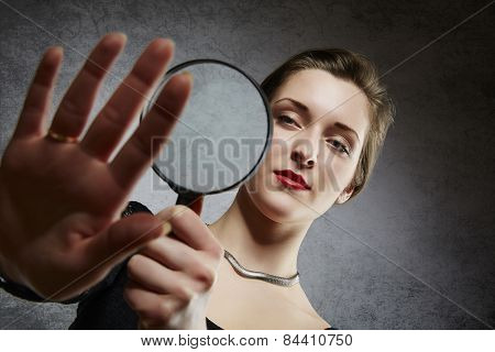 Beautiful woman examining her engagement ring through magnifying glass