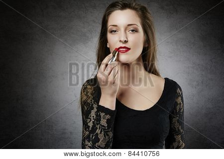 Beautiful woman making up her lips