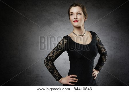 Smiling fashion model in black lace dress