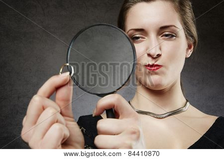 Suspicious woman looking at her wedding ring through magnifying glass