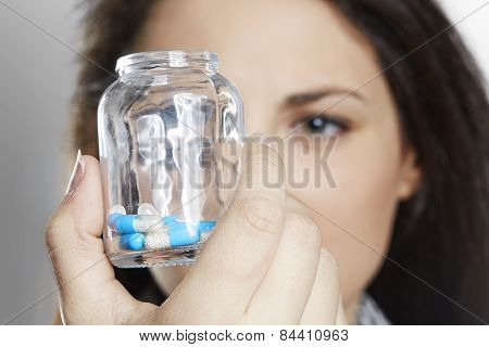 Close up of woman holding pill container