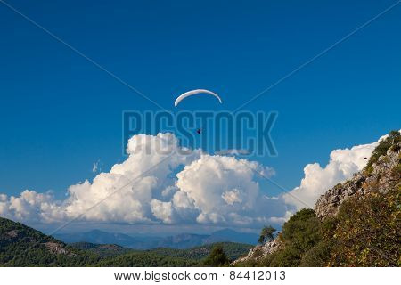 Paraglider flying over sky and mountains in summer day Oludeniz Turkey