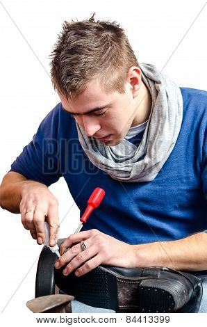 Young Shoemaker Repairing A Old Pair Of Shoes With A Tool Isolated On White Background