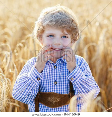 Funny Little Kid Boy In Leather Shors, Walking  Through Wheat Field