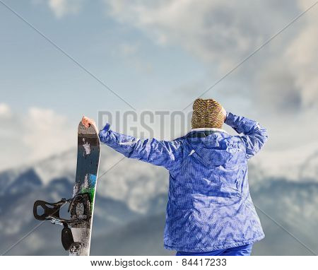 Woman With Snowboard Looks On The Snow Mountain