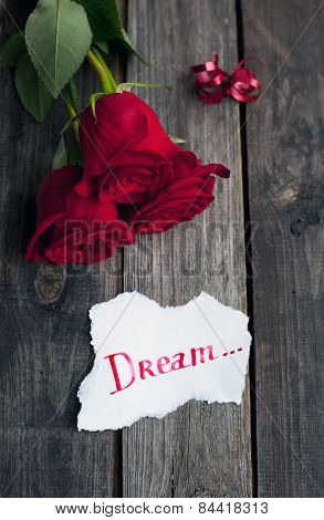 Three Red Roses On Rustic Table With Handwritten Word Dream