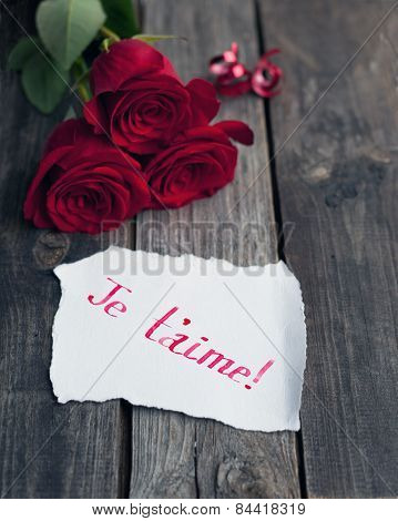 Three Red Roses On Rustic Table With Handwritten Words Je T'aime